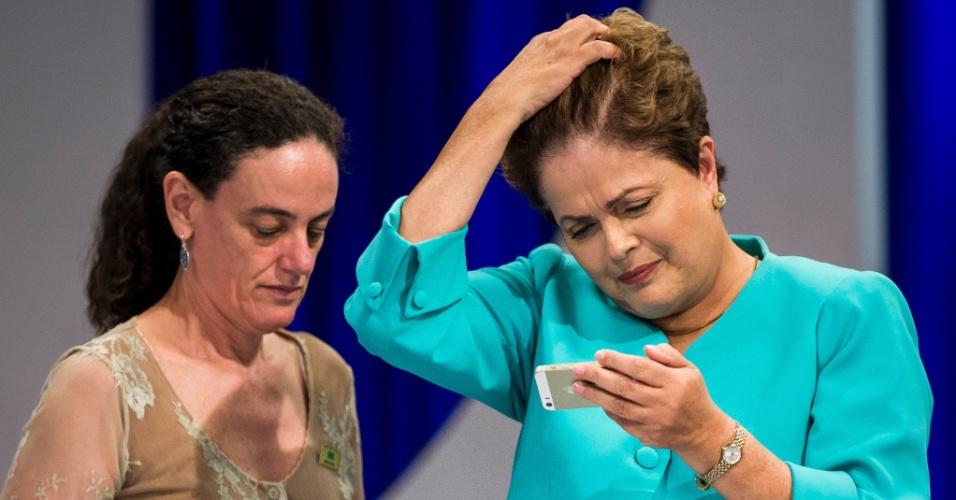 16.out.2014 - A presidente Dilma Rousseff, candidata à reeleição pelo PT, olha para smartphone enquanto mexe no cabelo durante intervalo de debate do segundo turno das eleições, promovido pelo UOL, SBT e Jovem Pan, nesta quinta-feira (16), no SBT, em São Paulo