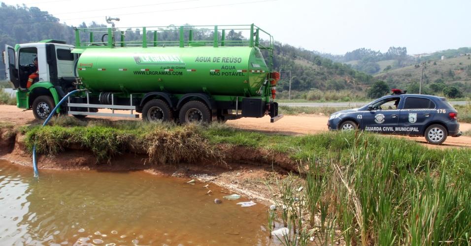 16.out.2014 - Um caminhão-pipa é flagrado por guardas municipais retirando água da lagoa do Foga, localizada às margens da rodovia Miguel Melhado, em Vinhedo, no interior de São Paulo. O dono do caminhão foi levado até a lagoa para devolver a água retirada