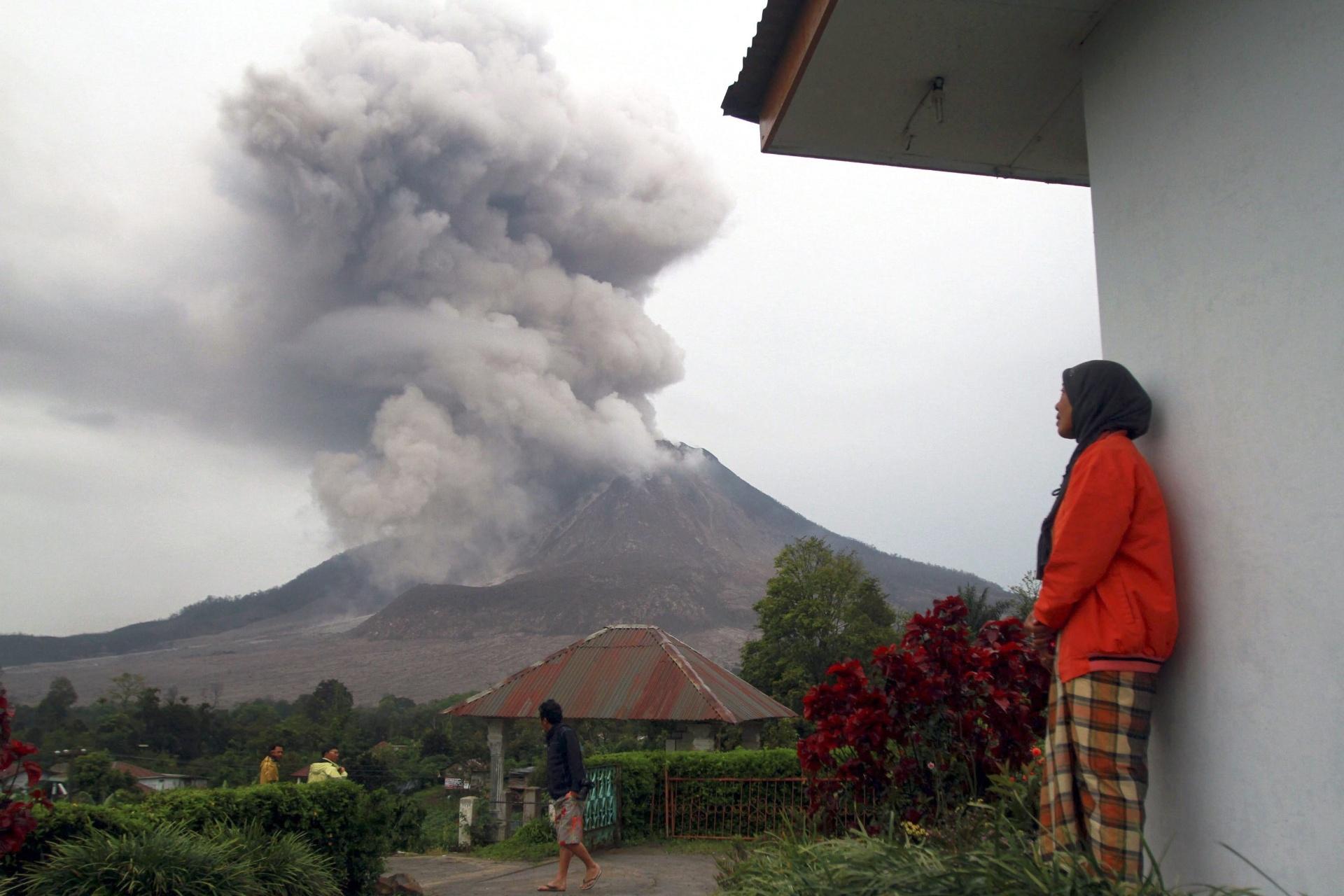 18.out.2014 - Mulher muçulmana observa erupção do monte Sinabung na vila de Tiga Pancur Village, Karo, no norte de Sumatra, Indonésia
