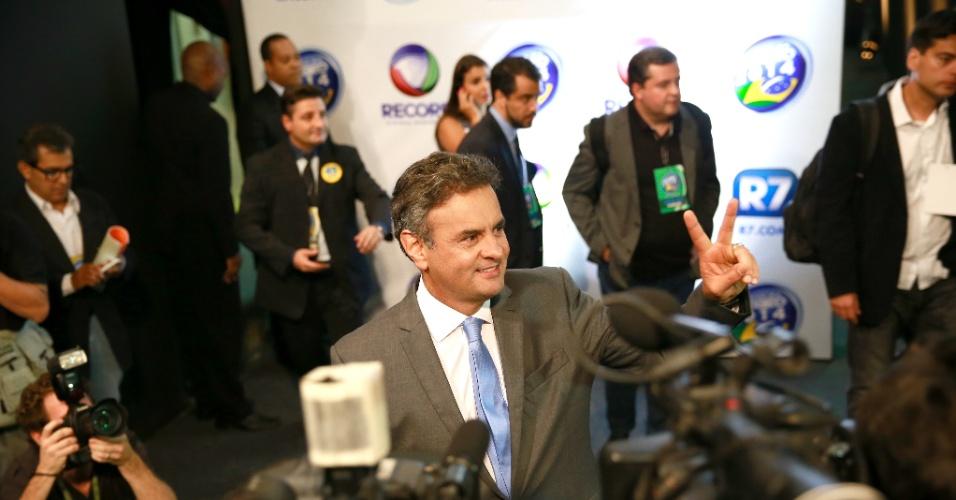 19.out.2014 - Aécio Neves, candidato do PSDB à Presidência da República, faz sinal de vitória ao chegar aos estúdios da Record, em São Paulo, onde participará de debate com a presidente Dilma Rousseff (PT), candidata à reeleição, neste domingo (19)
