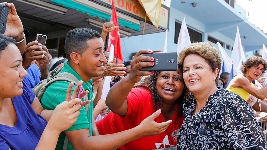 20.out.2014 - A presidente Dilma Rousseff, candidata à reeleição pelo PT, tira selfie com eleitora durante carreata em Nova Iguaçu, no Rio de Janeiro