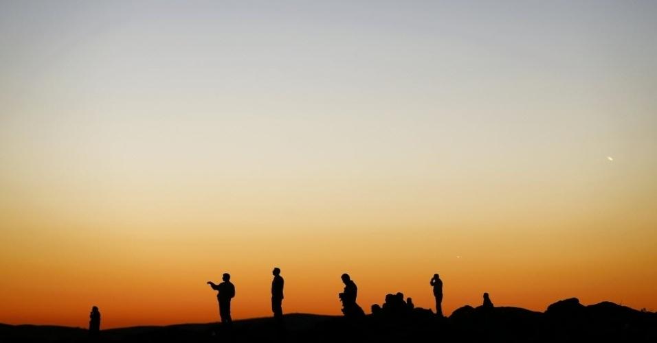 20.out.2014 - Curdos assistem a ataque do Estado Islâmico à cidade síria de Kobane, a partir de uma colina no lado turco da fronteira.