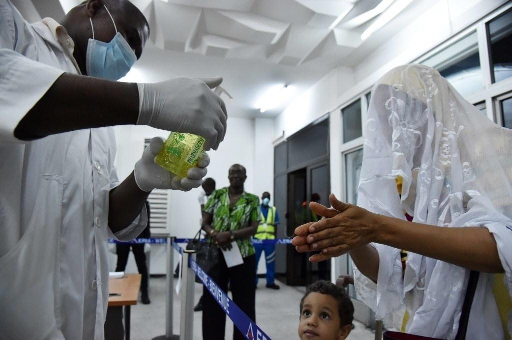 20.out.2014 - Membro de equipe médica desinfeta um passageiro que chega de Conacri, na Guiné, no aeroporto de Abidjan, na Costa do Marfim, nesta segunda-feira (20). A companhia aérea da Costa do Marfim retomou os voos para os três países da África Ocidental atingidos pela epidemia de ebola