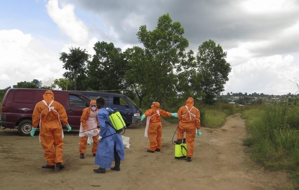 20.out.2014 - Membros da Cruz Vermelha desinfetam, nesta segunda-feira (20), área em que foram encontrados os corpos abandonados de uma mulher de 80 anos e sua neta, que estariam infectadas com o vírus ebola, em Serra Leoa
