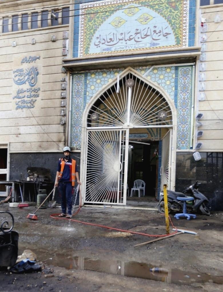 20.out.2014 - Trabalhador limpa o local onde um carro-bomba explodiu, em Bagdá, no Iraque. Forças iraquianas tentar avançar em áreas no nordeste do país controladas pelo grupo extremista Estado Islâmico