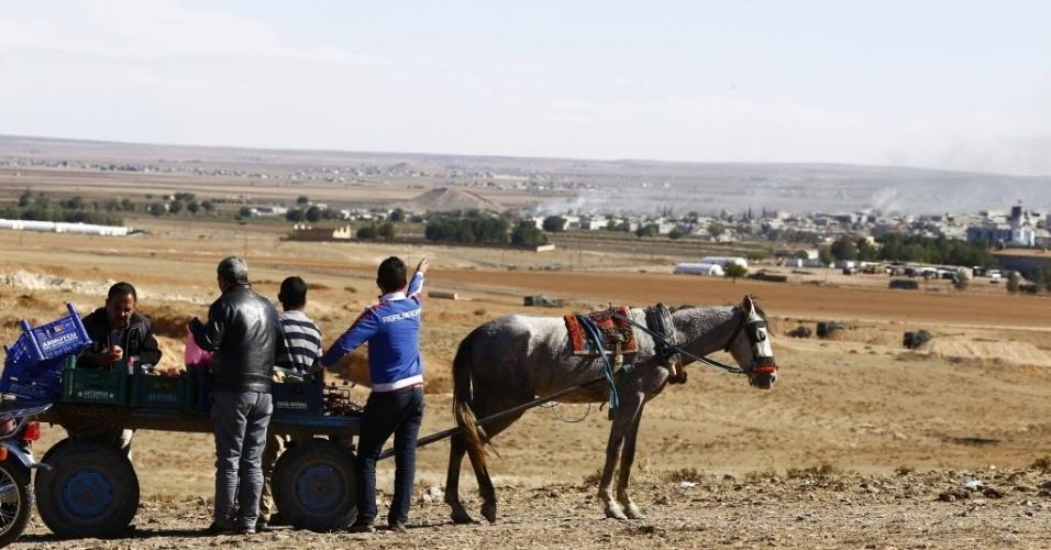 Curdos em colina próxima à cidade turca de Suruc observam a cidade síria de Kobane, na fronteira com a Turquia. Kobane está sob ataque de radicais do Estado Islâmico, combatidos pelos curdos.
