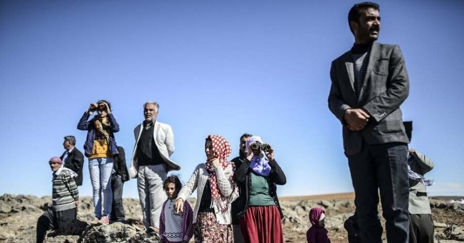 Membros da família curda síria Altay, na vila turca Mursitpinar, usam binóculo para tentar enxergar um parente que luta contra os jihadistas do Estado Islâmico na cidade síria de Kobane
