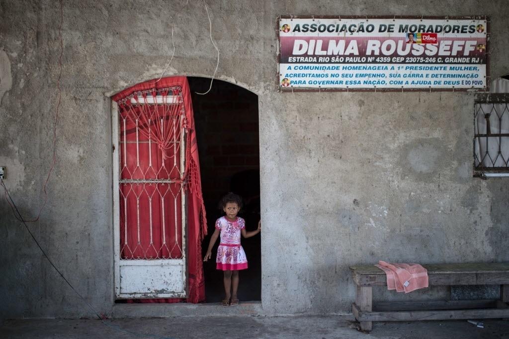 20.out.2014 - Menina é vista em uma casa na favela Dilma Rousseff, em Campo Grande, zona oeste do Rio de Janeiro, com placa que mostra o apoio de moradores à presidente