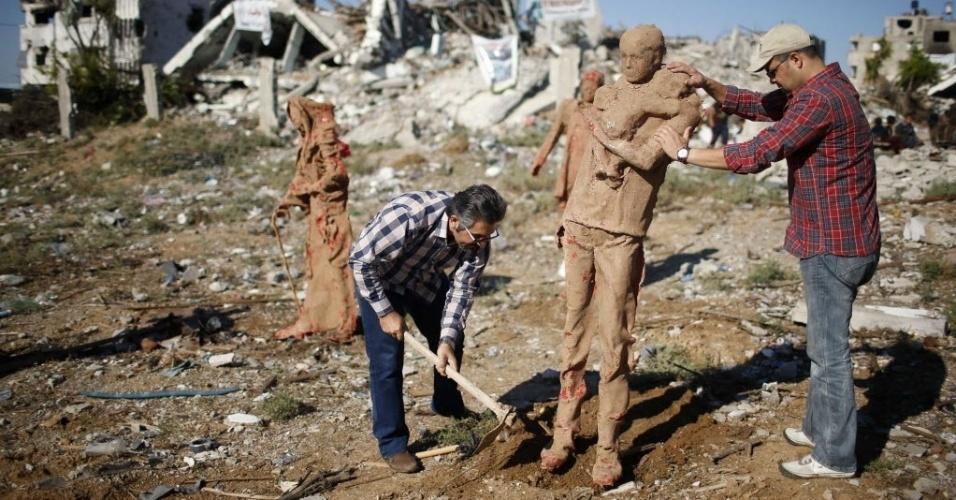 21.out.2014 - Artista palestino Eyad Sabbah (esquerda) posiciona uma estátua feita de fibra de vidro e coberta com argila, que representa palestinos que fugiram de suas casas durante bombardeios israelenses nos conflitos que ocorreram entre julho e agosto deste ano em Gaza