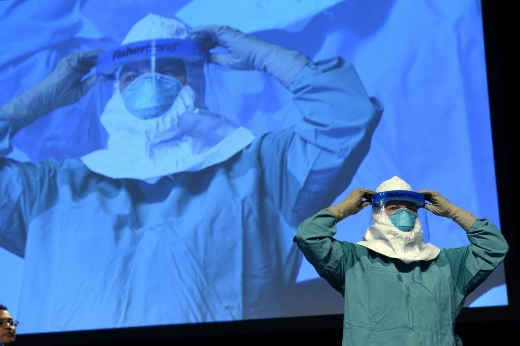 21.out.2014 - Funcionários de saúde mostram a maneira correta de colocar o traje de proteção para evitar a contaminação pelo ebola durante um seminário para médicos e enfermeiros no centro de convenções Javits, em Nova York, nos Estados Unidos
