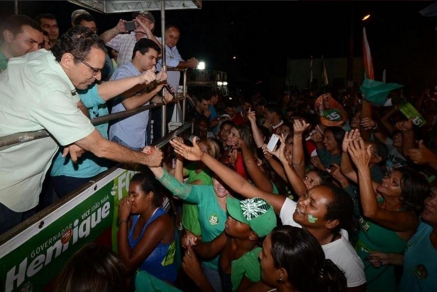21.out.2014 - O candidato do PMDB ao governo do Rio Grande do Norte, Henrique Alves (à esq.), estende o braço para eleitoras durante carreata nesta segunda-feira (20), na zona rural Traíras, em Macaíba. Alves, que é deputado federal, disputará o segundo turno com Robinson Faria (PSD), vice-governador do Estado. O peemedebista terminou o primeiro turno com 47,34% dos votos válidos, contra 42,04% de seu adversário do PSD
