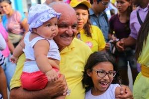 21.out.2014 - O governador do Amazonas e candidato à reeleição, José Melo (PROS), posou para fotos com crianças durante passeata no bairro Monte das Oliveiras, em Manaus, nesta segunda-feira (20). A pesquisa Ibope do segundo turno do governo divulgada na sexta-feira (17), mostrou empate técnico entre Eduardo Braga (PMDB) e Melo. O candidato do PROS aparece na frente com 53% dos votos válidos, contra 47% de Braga