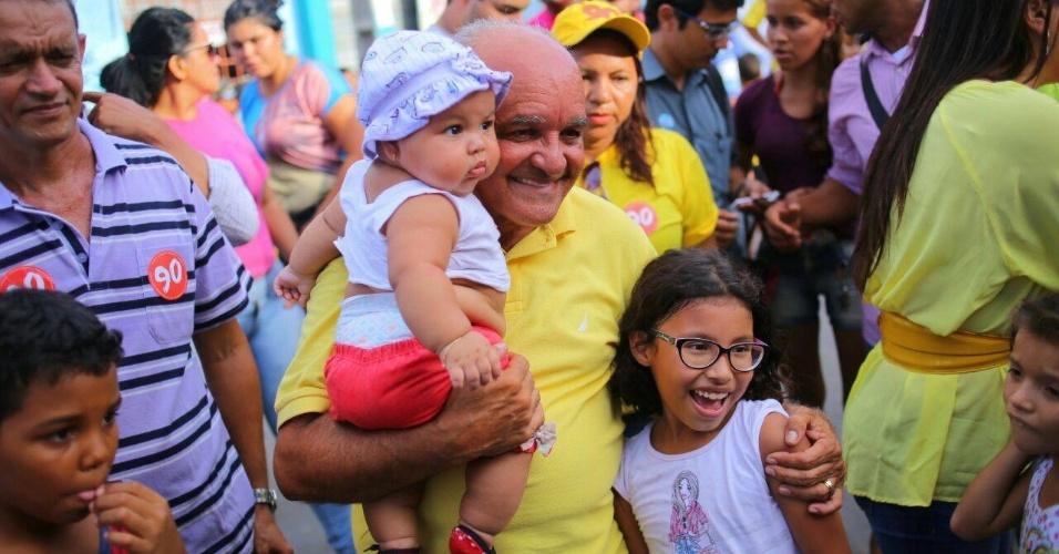 21.out.2014 - O governados do Amazonas e candidato à reeleição, José Melo (PROS), posou para fotos com crianças durante passeata no bairro Monte das Oliveiras, em Manaus, nesta segunda-feira (20). A pesquisa Ibope do segundo turno do governo divulgada na sexta-feira (17), mostrou empate técnico entre Eduardo Braga (PMDB) e Melo. O candidato do PROS aparece na frente com 53% dos votos válidos, contra 47% de Braga