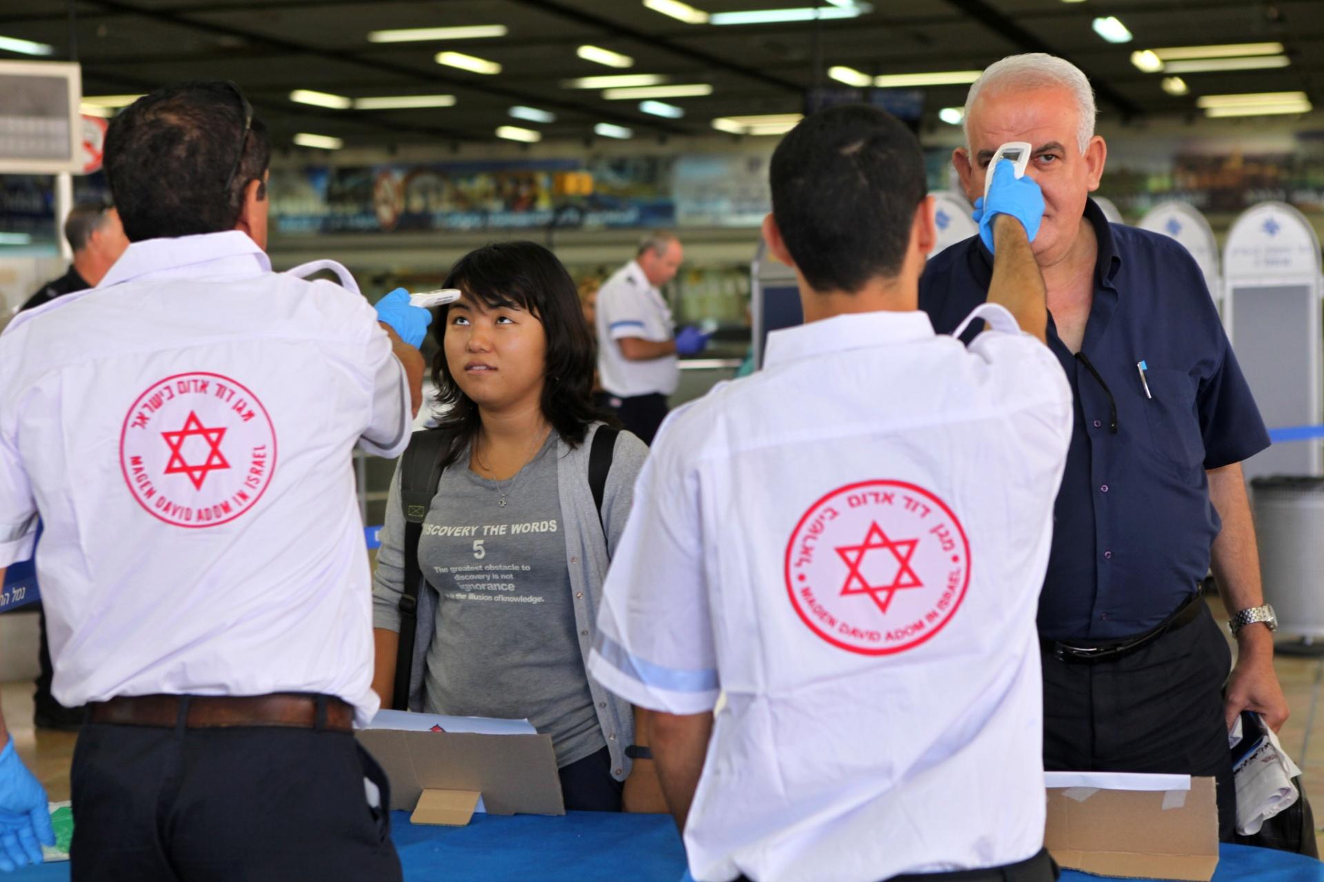 21.out.2014 -  Paramédicos israelenses medem a temperatura de passageiros que chegam ao aeroporto Ben Gurion, em Tel Aviv, provenientes do Cairo, no Egito. Israel expandiu o controle de fronteiras para evitar uma possível entrada no país de pessoas contaminadas por ebola