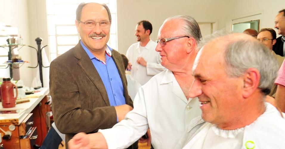 21.out.2014- O candidato ao governo do Rio Grande do Sul, José Ivo Sartori (PMDB) (à esq.), entrou em barbearia para conversar com eleitores durante caminhada por Caxias do Sul nesta segunda-feira (20). De acordo com o levantamento divulgado pelo Datafolha na quinta-feira (16), Sartori lidera as intenções de voto com 60% dos votos válidos, contra 40% do atual governador, Tarso Genro (PT)