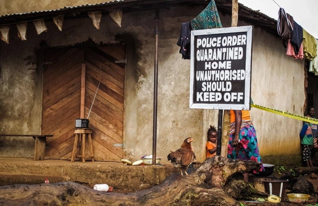 22.out.2014 - Criança e mulher ignoram aviso de quarentena por causa de ebola em casa de Serra Leoa