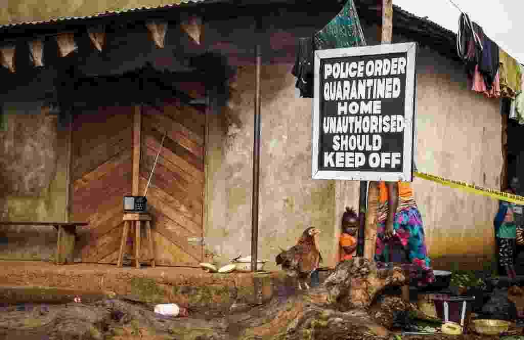 22.out.2014 - Criança e mulher ignoram aviso de quarentena por causa de ebola em casa de Serra Leoa - Michael Duff