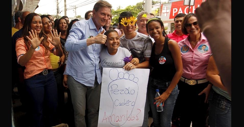 22.out.2014 - O senador e candidato ao governo do Rio de Janeiro, Marcelo Crivella (PRB), faz campanha em Bacaxá, na cidade de Saquarema (RJ). Eleitores seguram cartaz com a pergunta