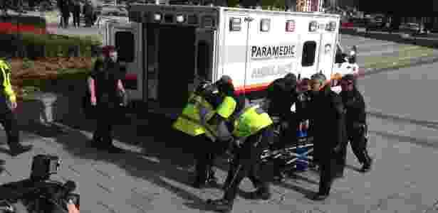 Policiais e paramédicos transportam homem ferido em tiroteio no Memorial da Guerra, em Ottawa, no Canadá - Michel Comte/AFP