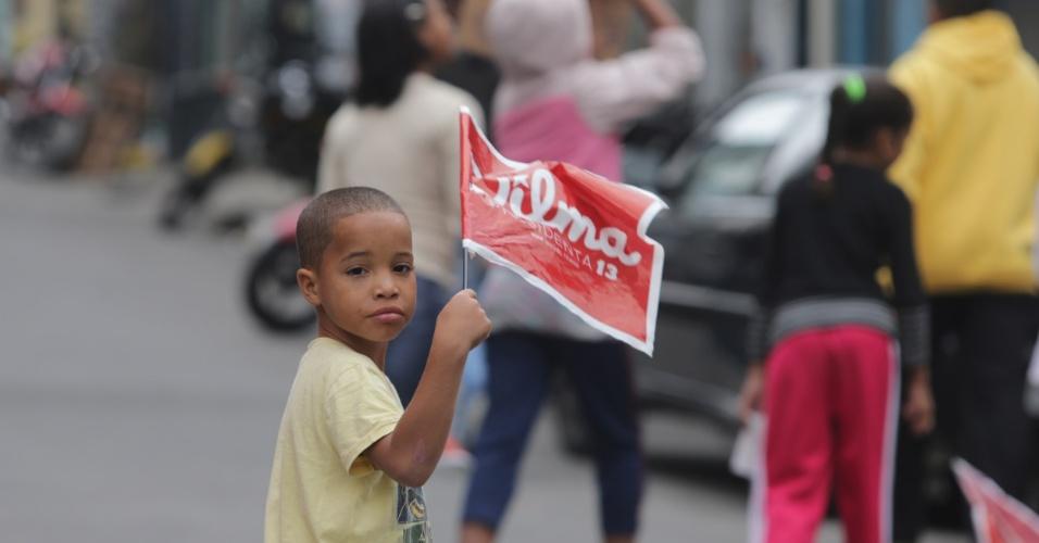 22.out.2014 - Menino segura bandeira de apoio à presidente e candidata à reeleição pelo PT, Dilma Rousseff, na favela Heliópolis, na zona sul de São Paulo
