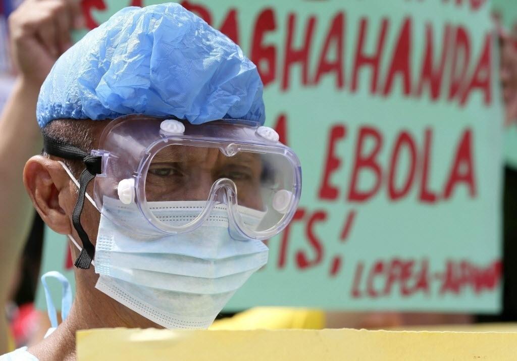 23.out.2014 - Profissionais de saúde filipinos se manifestam contra o governo na porta de um hospital público destinado a receber pacientes com ebola em Manila