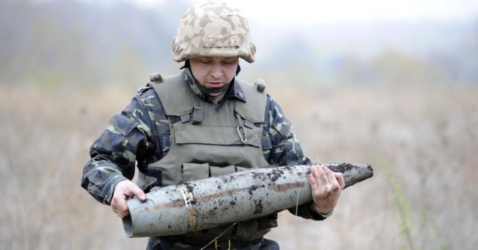 23.out.2014 - Soldado ucraniano carrega uma bomba que não detonou durante os trabalhos de remoção de minas em um campo perto da zona de Novoazovsk, nas proximidades da cidade de Mariupol, na Ucrânia, nesta quinta-feira (23). No próximo domingo (26), a Ucrânia realizará suas primeiras eleições legislativas desde a mudança de poder, ocorrida em fevereiro, imersa em um conflito armado no leste do país, onde os separatistas pró-Rússia boicotarão a votação nas regiões em seu controle