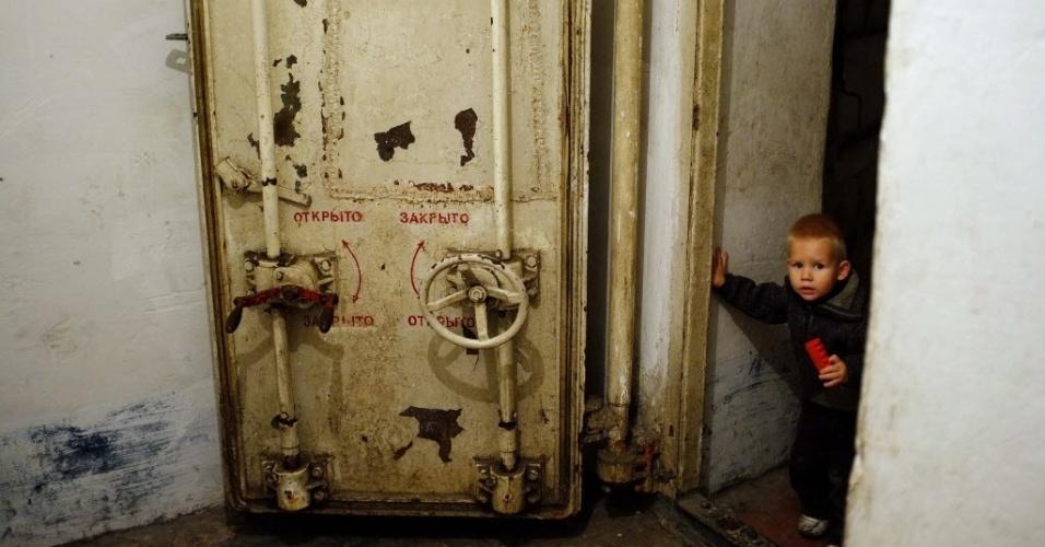 23.out.2014 - Um menino olha para fora da porta de um abrigo onde pessoas buscam refúgio dos bombardeios constantes em Petrovski, próximo a Donetsk, na Ucrânia, nesta quinta-feira (23). No próximo domingo (26), a Ucrânia realizará suas primeiras eleições legislativas desde a mudança de poder, ocorrida em fevereiro, imersa em um conflito armado no leste do país, onde os separatistas pró-Rússia boicotarão a votação nas regiões em seu controle