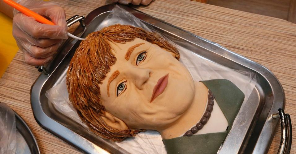 23.out.2014 - Yelena Zelenskaya, artista russa, finaliza torta que assou no formato do rosto de Angela Merkel, chanceler alemã. O nome da obra é