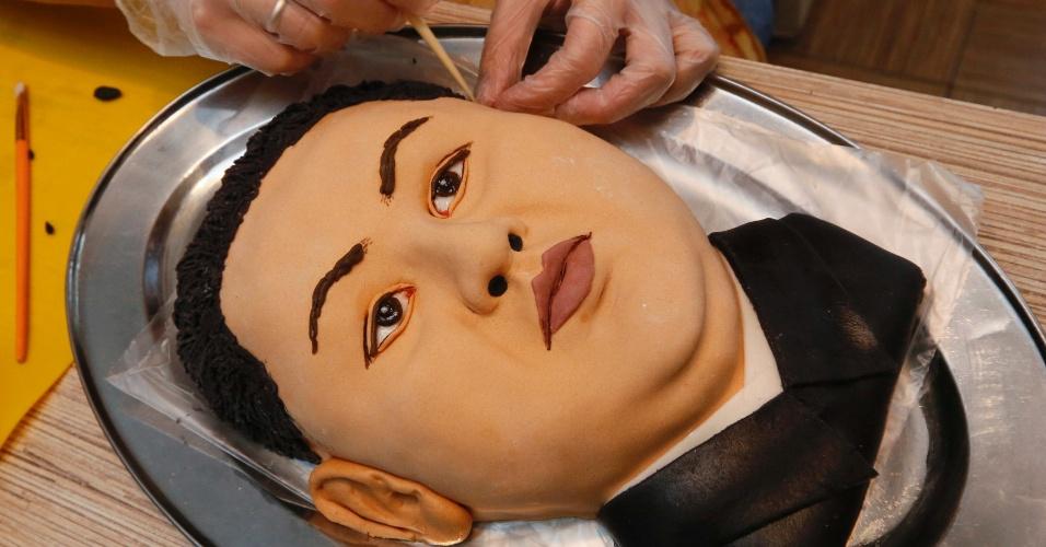 23.out.2014 - Yelena Zelenskaya, artista russa, finaliza torta que assou no formato do rosto de Kim Jong-Un, líder norte-coreano. O nome da obra é