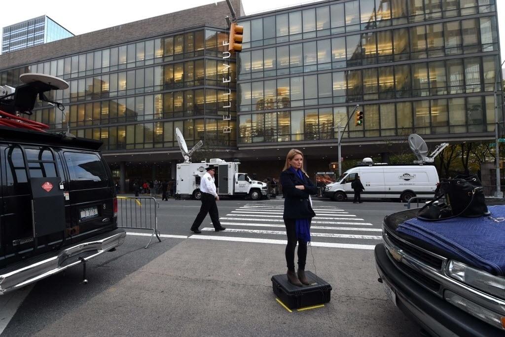 24.out.2014 - Jornalista se posiciona a frente do hospital Bellevue, em Nova York, onde o médico norte-americano Craig Spencer está internado em área isolada, após exame confirmar que ele tem ebola. Craig tratou de doentes com a doença na Guiné, um dos países que vive a epidemia do vírus