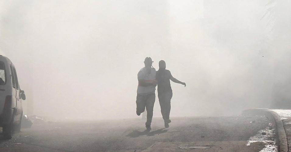 24.out.2014 - Manifestantes palestinos correm para fugir de bombas de gás lacrimogêneo disparadas por policiais israelenses durante confrontos após um protesto no bairro de Issawiya, em Jerusalém