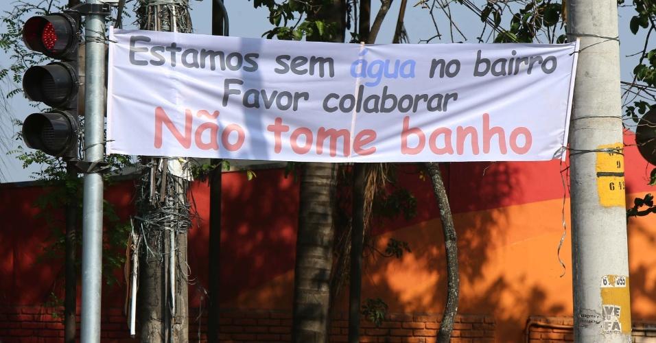 24.out.2014 - Moradores do bairro Helena Maria, em Osasco (SP), estendem faixa em que pedem para a vizinhança evitar tomar banho devido à falta de água