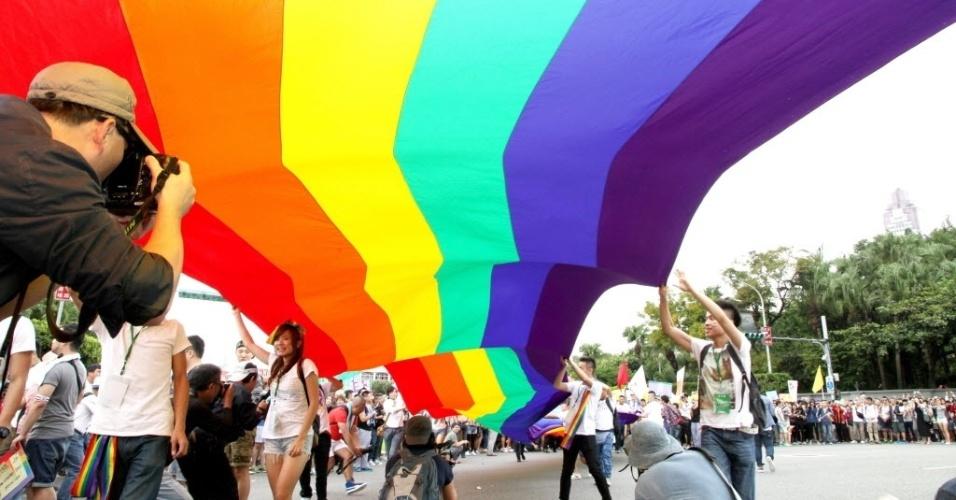 25.out.2014 - Foliões seguram bandeira gigante com as cores do arco-íris, que representa o movimento LGBT, durante a 12ª parada do orgulho gay em Taipé, Taiwan, na China, neste sábado (25). Participantes de toda a China, Japão e Tailândia apoiam os direitos das minorias sexuais ao participar do evento, que é o  maior do tipo na Ásia