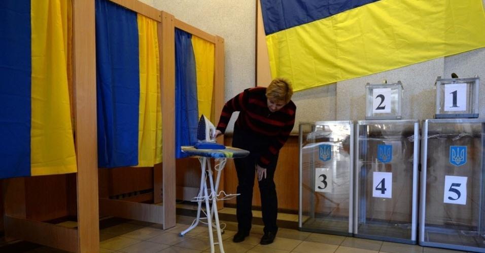 25.out.2014 - Mulher passa ferro em bandeiras da Ucrânia para acabar de preparar o local de votação para as eleições ucranianas em Kiev, neste sábado (25). Os separatistas pró-Rússia vão organizar boicotes em 15 das 32 zonas eleitorais existentes nas regiões de Donetsk e Lugansk, controladas por eles, durante as eleições legislativas que serão realizadas no domingo (26) na Ucrânia
