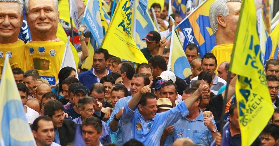 25.out.2014 - O candidato à reeleição ao governo de Goiás, Marconi Perillo (PSDB, centro), faz sinal para eleitores durante caminhada neste sábado