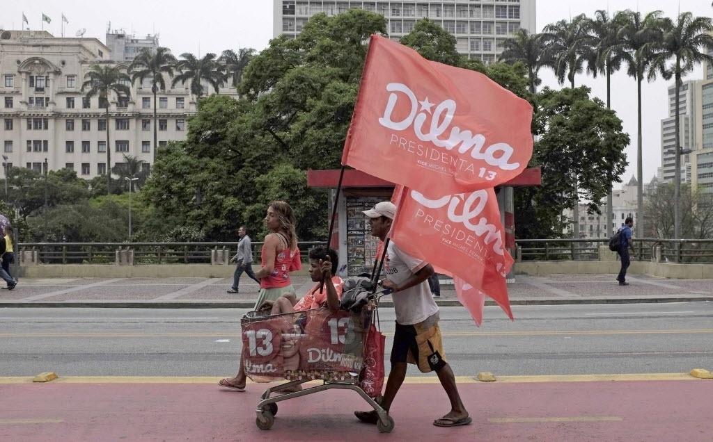 25.out.2014 - Um homem e uma mulher usam um carrinho com adesivos de campanha e bandeiras para apoiar a presidente e candidata à reeleição pelo PT, Dilma Rousseff, em São Paulo. Pesquisa do Ibope divulgada neste sábado, véspera do segundo turno das eleições, mostra que Dilma será reeleita ao derrotar o senador Aécio Neves (PSDB). Já o Datafolha, que também divulgou pesquisa hoje, aponta uma indefinição já que os dois aparecem empatados tecnicamente no limite da margem de erro, com a petista numericamente à frente