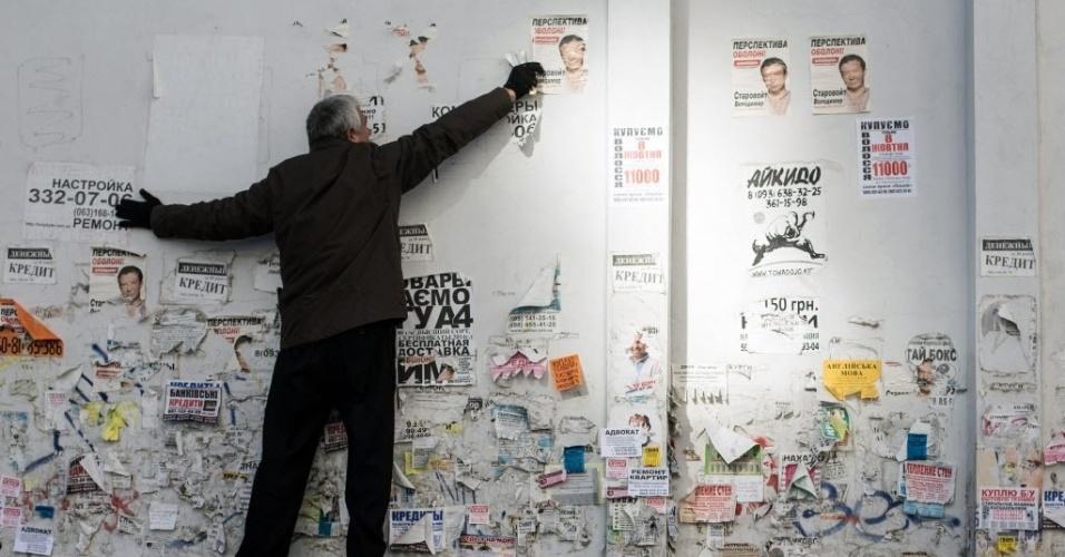 25.out.2014 - Voluntário remove propaganda eleitoral na véspera das eleições parlamentares, em Kiev, na Ucrânia, neste sábado (25)