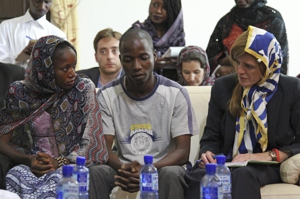 26.out.2014 - A embaixadora dos Estados Unidos, Samantha Power, se encontra com os sobreviventes do ebola, Fanta Oulen Camara, 24, e Oulare Bakary, 30, na Guiné. Power está em viagem pelos países afetados pelo vírus na África