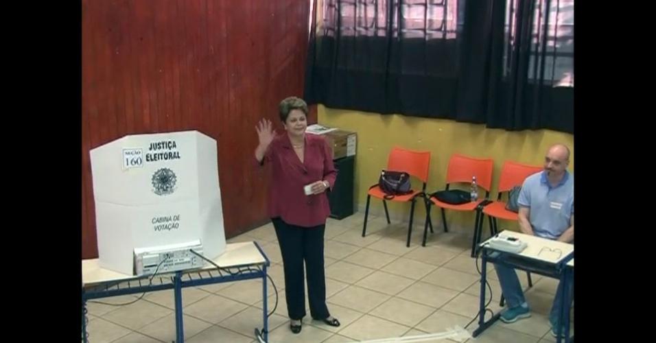 26.out.2014 - A presidente e candidata a reeleição Dilma Rousseff (PT) acena para jornalistas após votar no segundo turno das eleições neste domingo (26). Dilma votou por volta de 8h45, na escola Santos Dumont, que fica na Vila Assunção, zona sul de Porto Alegre (RS)