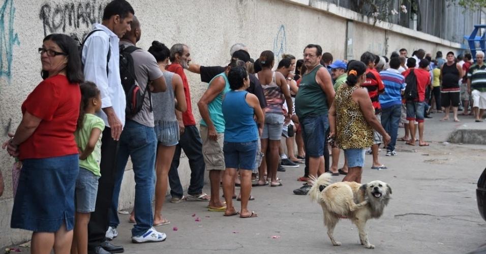 26.out.2014 - Eleitores fazem fila em frente a colégio eleitoral no complexo de favelas da Maré, no Rio de Janeiro, neste domingo