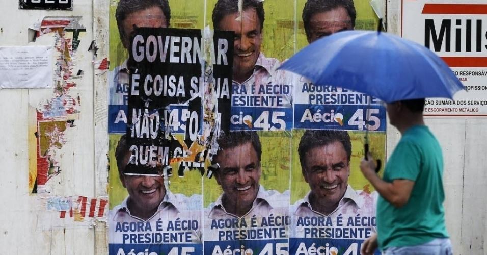 26.out.2014 - Homem passa em frente a uma parede coberta com cartazes danificados do candidato à Presidência Aécio Neves (PSDB), próximo a um colégio eleitoral, em Belo Horizonte, neste domingo
