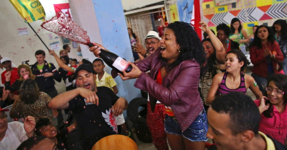 26.out.2014 - Membros do MTST (Movimento dos Trabalhadores Sem-Teto) e partidários da presidente reeleita Dilma Rousseff (PT) comemoram a vitória da petista no segundo turno das eleições presidenciais, no centro de São Paulo, neste domingo (26)