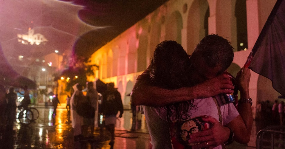 26.out.2014 - Militantes do PT se abraçam durante comemoração da reeleição da presidente Dilma Rouseff (PT) no Arco da Lapa no Rio de Janeiro (RJ), na noite deste domingo (26)