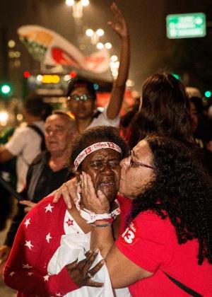 26.out.2014 - Mulheres se abraçam e choram durante comemoração do resultado do segundo turno das eleições presidenciais, na avenida Paulista, em frente ao prédio da Gazeta, na região central de São Paulo, neste domingo (26). A presidente Dilma Rousseff (PT) foi reeleita