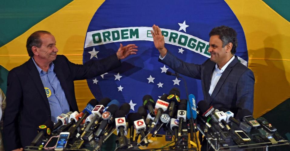 26.out.2014 - O candidato derrotado à Presidência pelo PSDB, Aécio Neves (dir.), cumprimenta seu candidato a vice na chapa, Aloysio Nunes (PSDB), em entrevista concedida após o reconhecimento da derrota para a candidata do PT, Dilma Rousseff neste domingo (26).