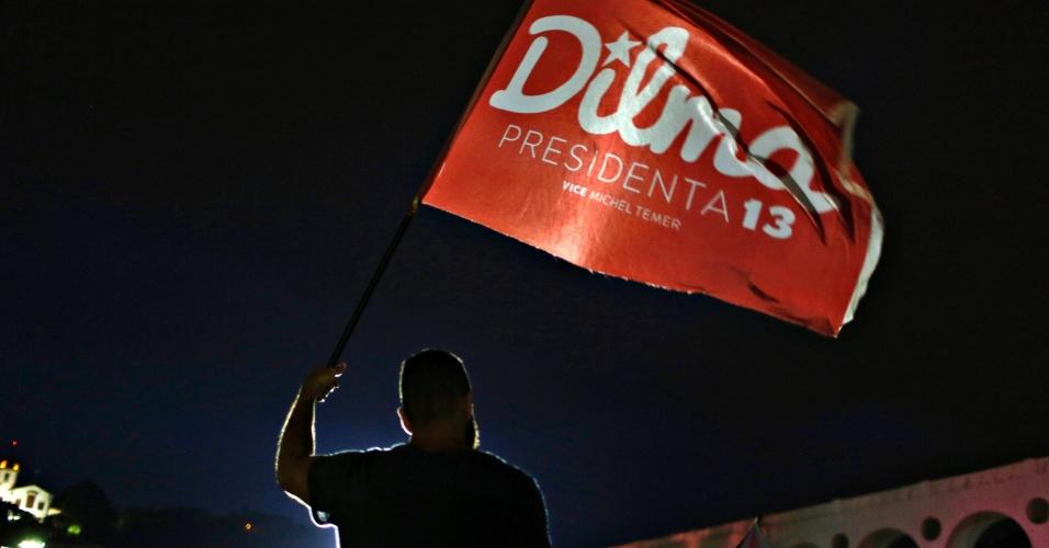 26.out.2014 - Partidário da presidente reeleita Dilma Rousseff (PT) segura uma bandeira antes de saber o resultados das eleições presidenciais, neste domingo (26), no Rio de Janeiro. Dilma Rousseff foi reeleita