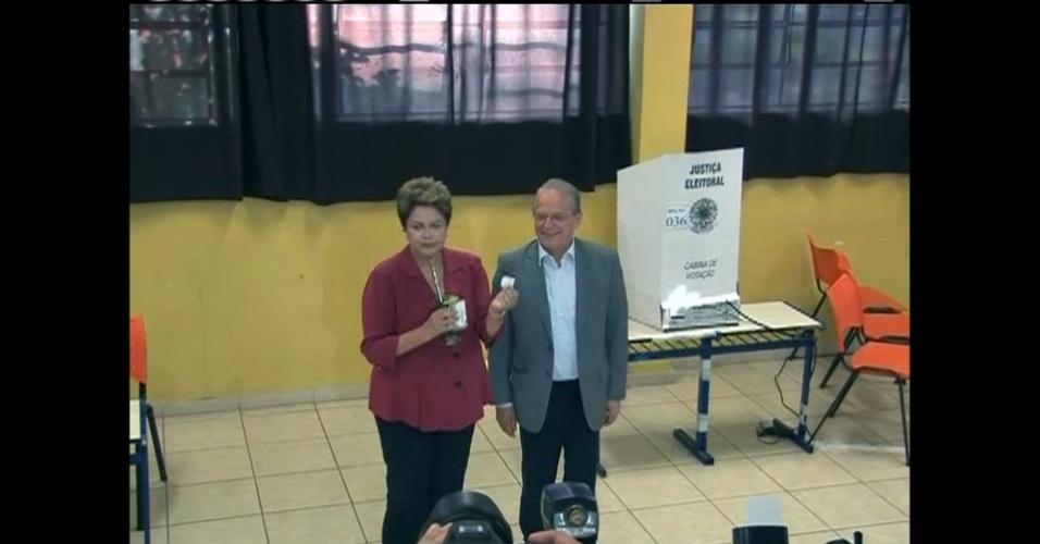 26.out.2014 - Tomando chimarrão, Dilma Rousseff (PT) vota na manhã deste domingo (26) no segundo turno das eleições. A presidente e candidata à reeleição compareceu ao seu colégio eleitoral, na zona sul de Porto Alegre (RS) acompanhada do candidato ao governo do Estado, Tarso Genro (PT)