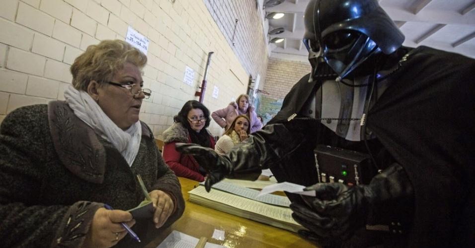 26.out.2014 - Um dos eleitores foi votar fantasiado do personagem Darth Vader, da série de filmes Guerra nas Estrelas, em um posto de votação em Kiev, na Ucrânia, neste domingo (26). O vilão dos filmes tentou ser candidato oficial do Partido da Internet Ucraniano, mas a comissão eleitoral rejeitou a candidatura do personagem as eleições