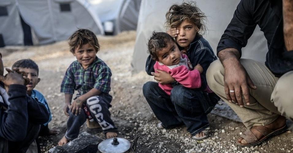 27.out.2014 - Crianças curdas se sentam em torno de pequena fogueira ao lado de fora de uma barraca no campo de refugiados de Rojava, em Suruc, na província de Sanliurfa, perto da cidade síria de Kobai, neste domingo (26). Na tentativa de acabar com ataques do grupo Estado Islâmico (EI) que assombram moradores locais, as forças militares americanas efetuaram entre este sábado e este domingo 12 ataques aéreos contra as posições do EI no Iraque e outros cinco na Síria, informou o Comando Central dos Estados Unidos