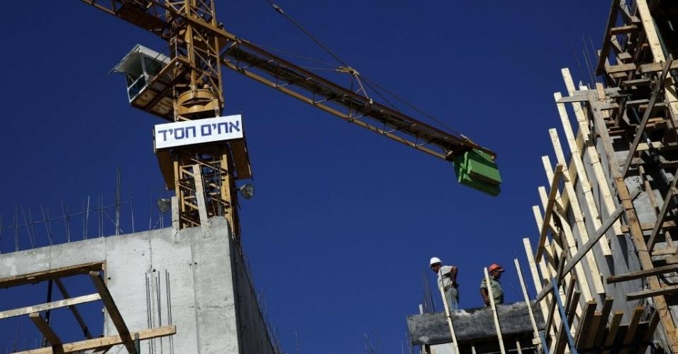27.out.2014 - Palestinos trabalham em um canteiro de obras de um novo projeto de habitação no oeste de Jerusalém. O governo israelense autorizou a construção de 1.000 novas casas de colonos judeus em uma anexo árabe de Jerusalém